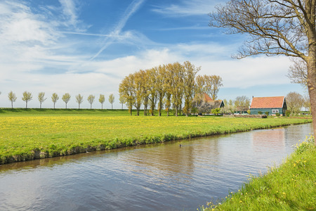 Reclaimed: Dike with a row of trees and farmhouse in the Beemster Polder  a cultural landscape located north of Amsterdam, dating from the early 17th century, and an exceptional example of reclaimed land in the Netherlands Editorial