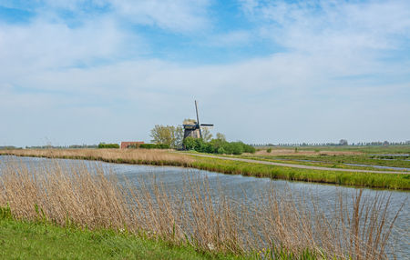 Typical Dutch polder landscape with mill and canal Editorial