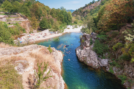 a bathing place: Thueyts, France, september 11, 2016: swimmers in the river Ardeche near the devils bridge in the village of Thueyts in the Ardeche department in France