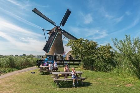 Kinderdijk, Netherlands, August 18, 2016: Tourists picnic at one of the mills at Kinderdijk.