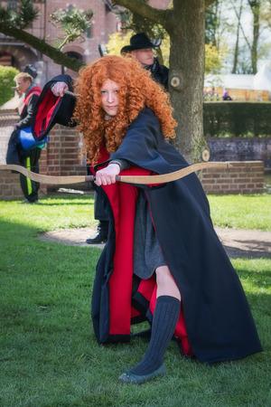 Haarzuilens, Países Bajos - 24 de abril de 2016: Chica pelirroja con handbow y varita mágica en el duende Fantasy Fair (Elfia), un evento de fantasía al aire libre en los países bajos.
