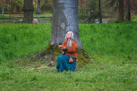 Haarzuilens, Países Bajos - 24 de abril de 2016: figura de la fantasía que come debajo de un árbol en el parque en Elf Fantasy Fair (Elfia), un evento al aire libre de la fantasía en los Países Bajos. Editorial