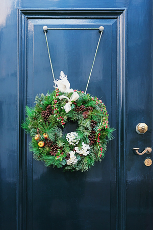 Christmas wreath attached to a blue door