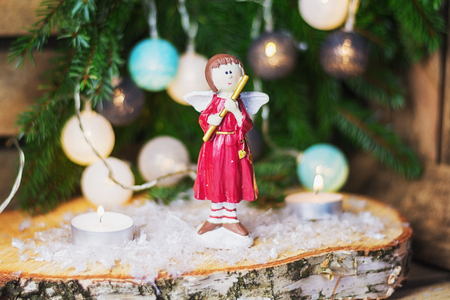 Angel with flute in front of a Christmas branch decorated with christmas balls