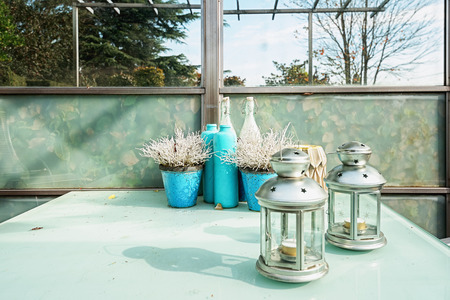 In the garden a modern table with decorative elements with a glass wall in the background