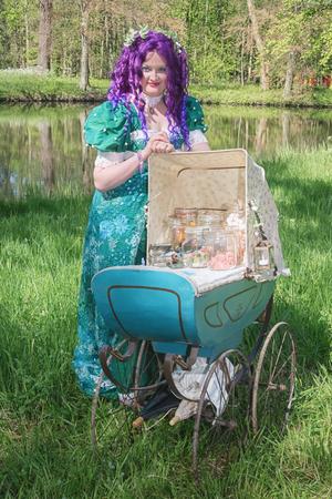 19 de abril de 2014, Haarzuilens, Países Bajos: Mujer vestida con una peluca morada y un cochecito antiguo lleno de frascos de vidrio con dulces durante la Elf Fantasy Fair (Elfia) es un evento de fantasía al aire libre en Castle de Haar