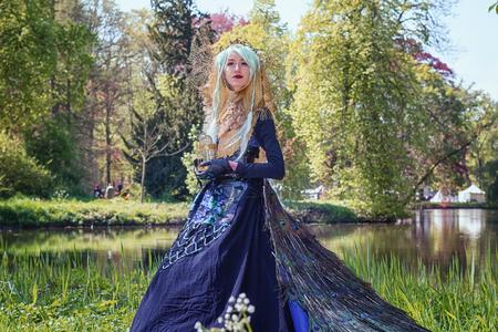 19 de abril de 2014, Haarzuilens, Países Bajos: Bella mujer vestida con un vestido de pavo real posa en el parque durante la Elf Fantasy Fair (Elfia) es un evento de fantasía al aire libre en Castle de Haar Editorial