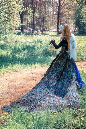 19 de abril de 2014, Haarzuilens, Países Bajos: Bella mujer vestida con un vestido de pavo real posa en el parque durante la Elf Fantasy Fair (Elfia) es un evento de fantasía al aire libre en Castle de Haar