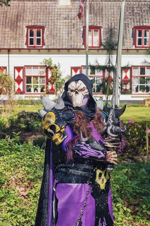19 de abril de 2014, Haarzuilens, Países Bajos: Hombre malvado con máscara de calavera y poses de espada enorme durante la Elf Fantasy Fair (Elfia) es un evento de fantasía al aire libre en Castle de Haar
