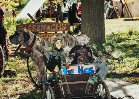 April  19, 2014, Haarzuilens, The Netherlands: Trolley filled with witch puppets pulled by a big dog during the Elf Fantasy Fair (Elfia) which is an outdoor fantasy event at Castle de Haar