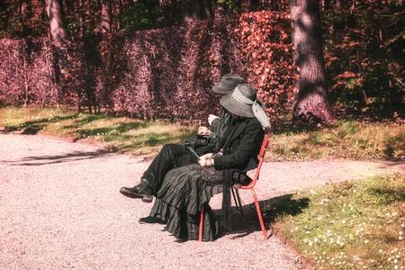 19 de abril de 2014, Haarzuilens, Países Bajos: pareja disfrazada disfruta del sol en un banco en el parque durante la Elf Fantasy Fair (Elfia) es un evento de fantasía al aire libre en Castle de Haar Editorial