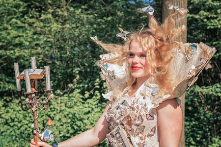19 de abril de 2014, Haarzuilens, Países Bajos: dama bellamente vestida con un vestido de papel decorado con mariposas posa en el parque durante la Elf Fantasy Fair (Elfia), que es un evento de fantasía al aire libre en Castle de Haar