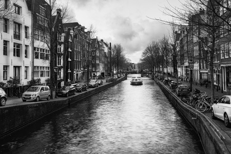 Amsterdam, The Netherlands, December 26, 2017: Black and white photo of a canal boat in the Brouwersgracht in the old center of Amsterdam Editorial