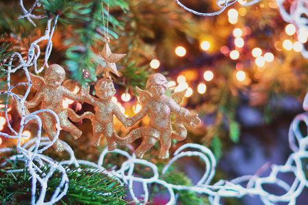 Christmas branch adorned with three golden cherubs