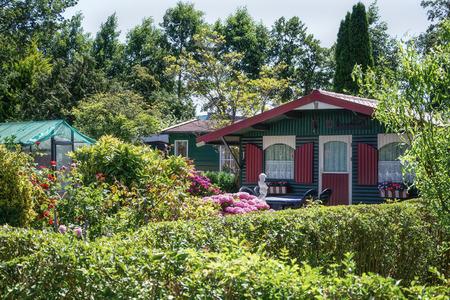 Zaandam, Niederlande, 2. Juli 2018: Gartenhaus und Gewächshaus, umgeben von einem schönen Ziergarten in den Niederlanden