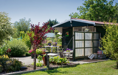 Zaandam, The Netherlands, July 2, 2018: Garden shed with greenhouse surrounded by a beautiful decorative garden in The Netherlands Editorial