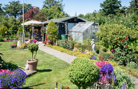 Zaandam, The Netherlands, July 2, 2018: Garden shed with greenhouse surrounded by a beautiful decorative garden in The Netherlands