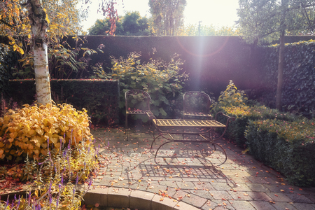Decorative iron garden chairs and table in the autumn sun in the corner of a garden in The Netherlands Stock Photo