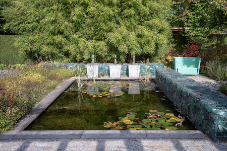 Pond surrounded by a wall made of glass blocks in a beautiful autumn garden somewhere in the Netherlands