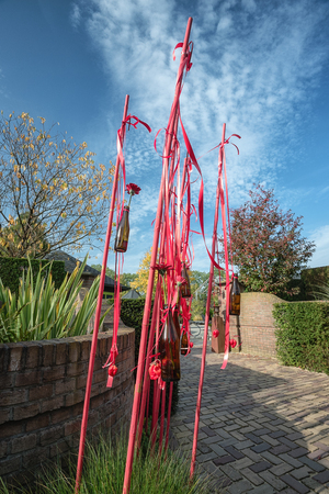 Nice idea to decorate the garden with red painted bamboo sticks with attached beer bottles filled with a red gerbera somewhere in a garden in the Netherlands Фото со стока