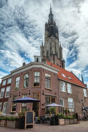 Delft, Netherlands, July 29, 2018:  Restaurant on the corner of Oudemanssteeg in Delft with in the background the church tower of De Nieuwe Kerk.