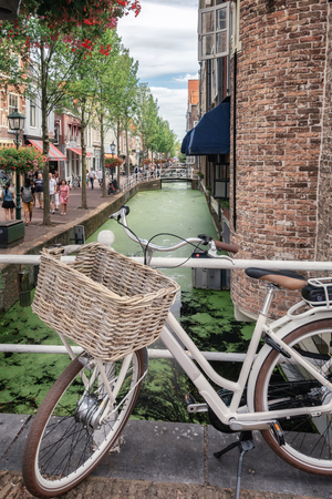 Delft, Netherlands, July 29, 2018: Ladies bike parked on a bridge over the Voldersgracht in the old center of Delft in the Netherlands.