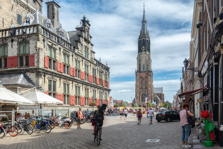Delft, Netherlands, July 29, 2018: The side and back of the City Hall in Delft with in the background the famous Nieuwe Kerk in which the royal crypt is located Editorial