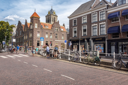 Delft, Netherlands, July 29, 2018: Impression of a street in the old center of Delft with the tower of the City Hall Delft in the background Editorial