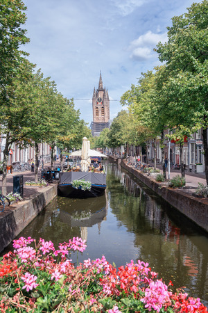 Delft, Netherlands, July 29, 2018: The Oude Delft canal in Delft with the Oude Kerk tower in the background. Editorial