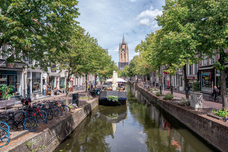Delft, Netherlands, July 29, 2018: The Oude Delft canal in Delft with the Oude Kerk tower in the background. 新聞圖片