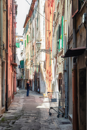 San Remo, Italy, September 18, 2018:  Man is pondering in the narrow street Via Bezzecca in the center of the Italian town San Remo