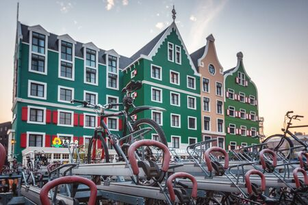 Zaandam, The Netherlands, April 18, 2019: Bicycle parking at Zaandam station with in the background the Zaanhotel in Zaandam built in the typical historical Zaanse building style