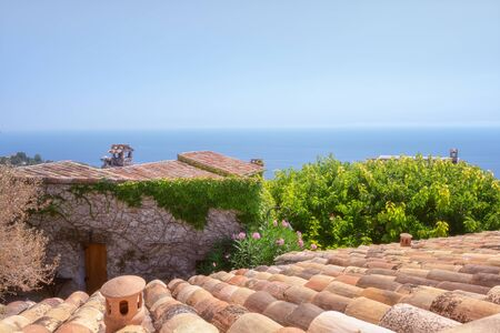 View on the Mediterranean Sea over the roofs of the picturesque medieval village of Eze in France
