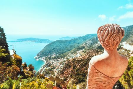 Beautiful view on the Mediterranean Sea with focus on the back of a statue in the botanical garden of medieval village Eze in France