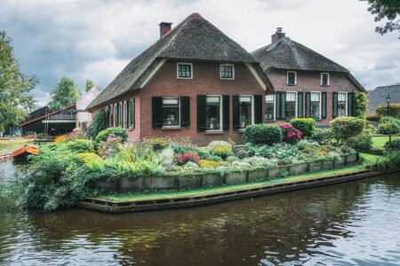 GIETHOORN, NETHERLANDS - August 17, 2017: known for its bridges, waterways, thatched cottages  and punters. It is also called the 'Dutch Venice' and known to the world Monopoly edition.