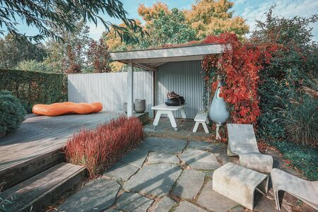 Trendy garden with terrace and overhang, decorated with trendy garden furniture and planters in an autumn garden somewhere in The Netherlands