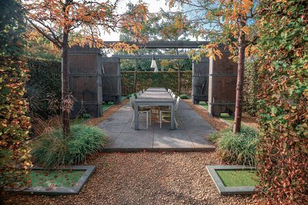 Trendy terrace with a long garden table in the garden of an autumn park in The Netherlands 版權商用圖片