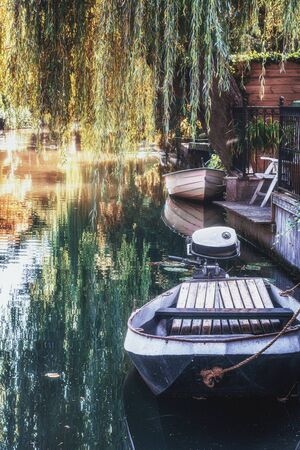 Small motor boat docked on the bank of the back garden in a canal in Edam in the Netherlands 版權商用圖片
