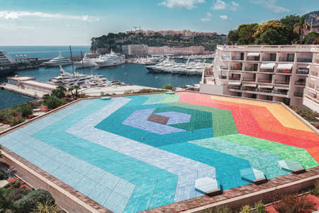 Monaco, September 14, 2018:   The colorful roof of the Rainier III auditorium with a the port Hercule of Monaco in the background Editoriali