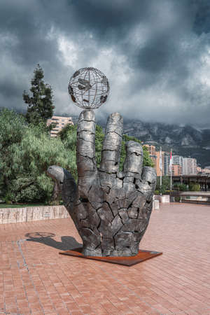 Monaco, September 14, 2018: Metal sculpture of a hand with a globe balancing on index finger Editoriali