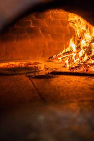 Original neapolitan pizza margherita in a traditional wood oven in restaurant