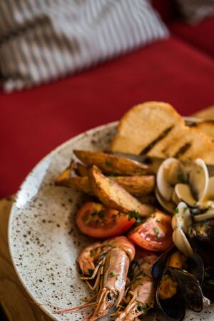 A plate with a variety of seafood stands on a table in a restaurant