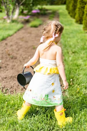 Happy toddler girl playing with watering cans outside. Spring is on the street. Girl stands with her back to the viewer