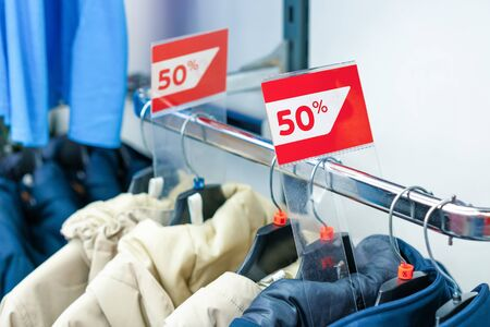 Sale sign 50 percent in a fashion clothes shop display window