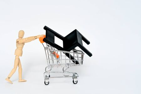 Wooden man carry supermarket shopping whith black chair in it isolated on white background. Arrangement of the apartment concept
