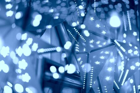 Festive background. Illuminated garlands of lights beautiful bokeh. Bright Christmas Street Illumination. New Year Lights Decorating. Toned in classic blue