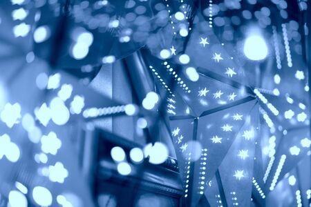 Festive background. Illuminated garlands of lights beautiful bokeh. Bright Christmas Street Illumination. New Year Lights Decorating. Toned in classic blue