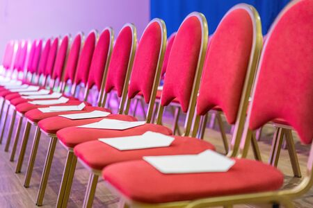 Rows of red chairs in conference hall, empty meeting or event room. Empty guest seats. Stock Photo