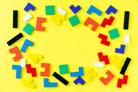 Frame from colorful different shapes wooden blocks on yellow background. Natural, eco-friendly toys for children. Creative, logical thinking concept. Flat lay. Copt space.