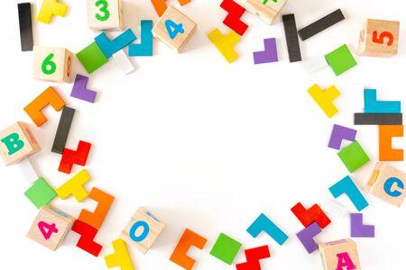 Rahmen aus bunten Holzklötzen verschiedener Formen auf weißem Hintergrund. Natürliches, umweltfreundliches Spielzeug für Kinder. Kreatives, logisches Denkkonzept. Flach liegen. Kopten Raum.